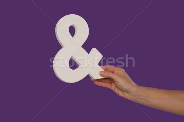 Female hand holding up an ampersand from the right Stock photo © stryjek