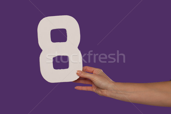Female hand holding up the number 8 from the right Stock photo © stryjek