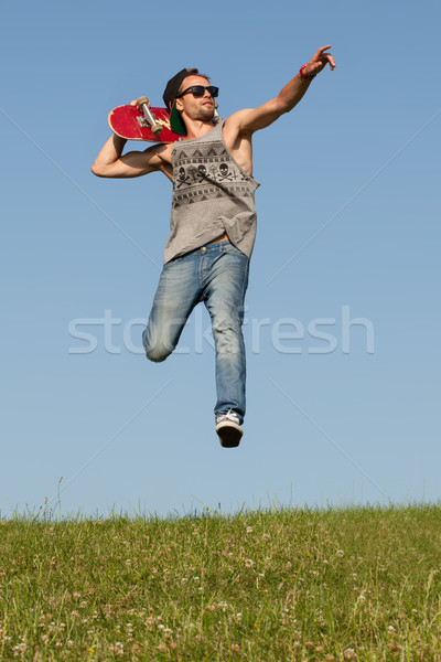 Man with a skateboard pointing and leaping Stock photo © stryjek