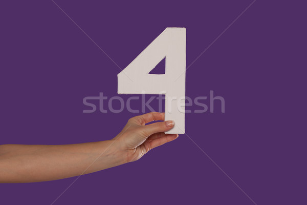 Female hand holding up the number 4 from the left Stock photo © stryjek