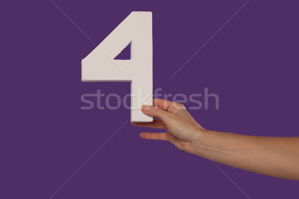 Female hand holding up the number 4 from the right Stock photo © stryjek