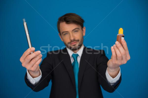 businessman holding e-cigarette and e-liquid on blue Stock photo © stryjek