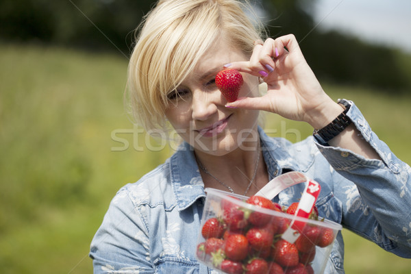 Woman holding up large ripe strawberry Stock photo © stryjek