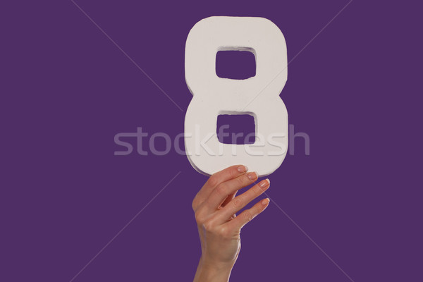 Female hand holding up the number 8 from the bottom Stock photo © stryjek