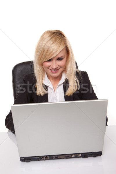 Efficient blonde businesswoman working on her laptop with her spectacles on the table alongside her Stock photo © stryjek