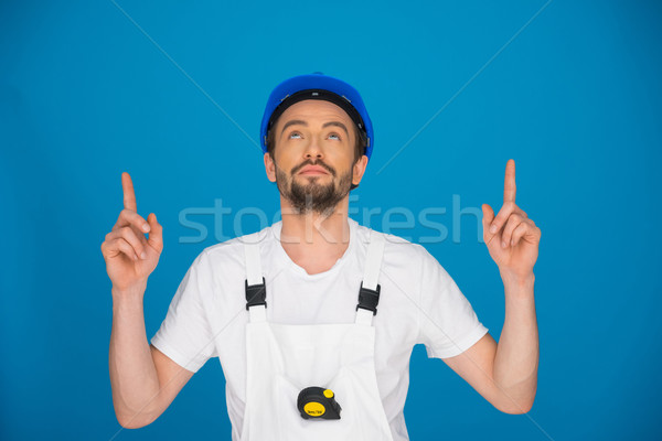 Workman in a hardhat pointing above his head Stock photo © stryjek