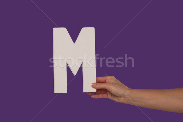 Female hand holding up the letter M from the right Stock photo © stryjek