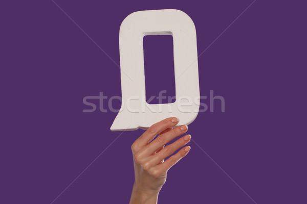 Female hand holding up the letter Q from the bottom Stock photo © stryjek