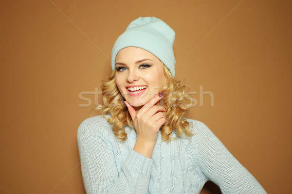Gorgeous young woman with blond ringlets in a green knitted winter outfit ,over light brown Stock photo © stryjek
