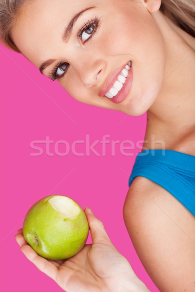 Smiling woman holding a bitten apple Stock photo © stryjek