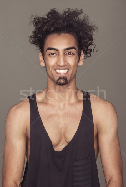Cheerful Curly-Haired Athletic Man Against Gray Stock photo © stryjek