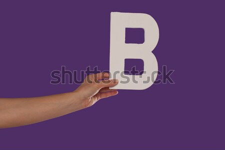 Female hand holding up the letter O from the left Stock photo © stryjek