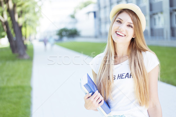 Cheerful Student Girl Holding Books at the Walkway Stock photo © stryjek