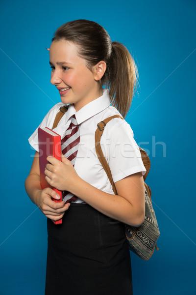 Boldog fiatal iskolás lány hordoz könyv iskolai egyenruha Stock fotó © stryjek