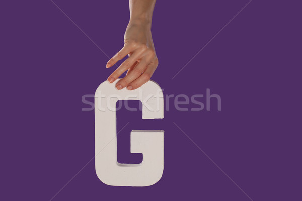 Female hand holding up the letter G from top Stock photo © stryjek