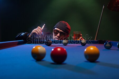 Man playing pool in a club smoking e-cigarette Stock photo © stryjek
