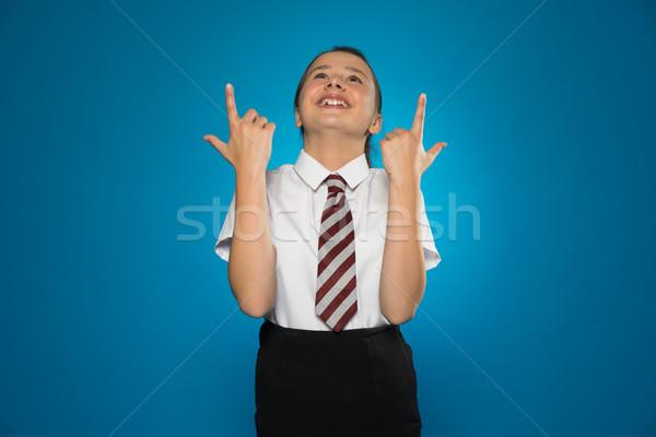 Boldog fiatal lány mutat fölött fej iskolai egyenruha Stock fotó © stryjek
