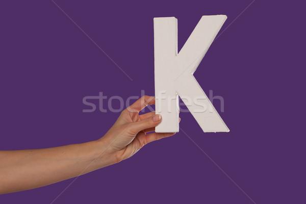 Female hand holding up the letter K from the left Stock photo © stryjek