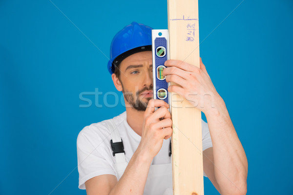 Builder holding a spirit level and plank of wood Stock photo © stryjek
