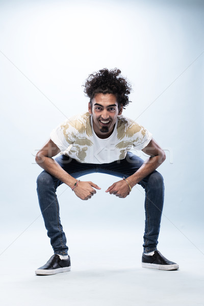 Smiling Hip Hop Dancer Squatting with Arm on Knees Stock photo © stryjek