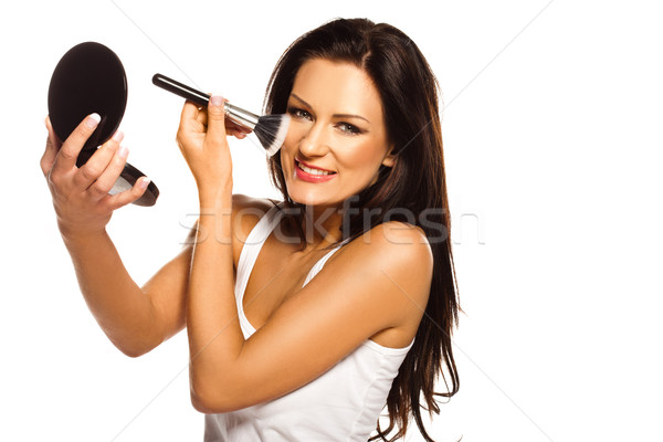 Beautiful woman applying blusher Stock photo © stryjek