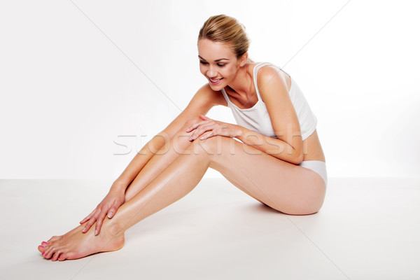 Beautiful woman caressing her legs Stock photo © stryjek