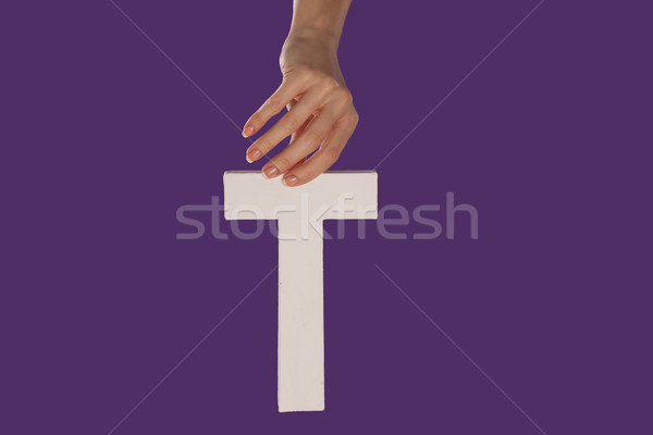 Female hand holding up the letter T from top Stock photo © stryjek