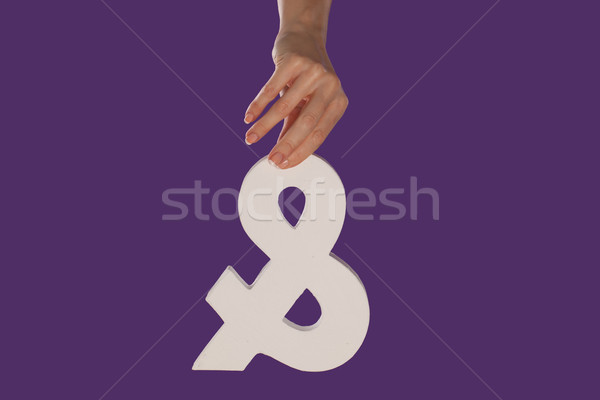 Female hand holding up an ampersand from the top Stock photo © stryjek