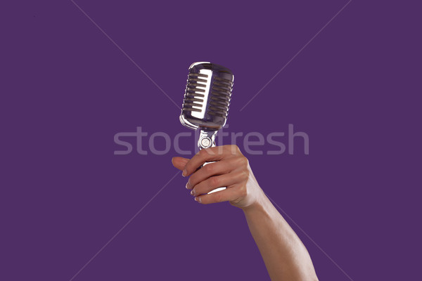 Female hand holding up a microphone Stock photo © stryjek