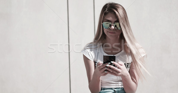 student wearing hat using her mobile to send a text Stock photo © stryjek