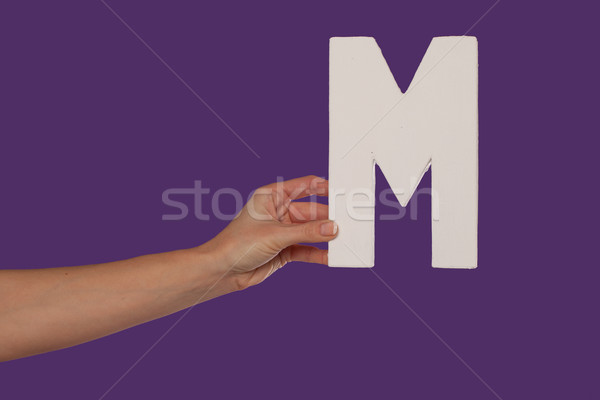 Female hand holding up the letter M from the left Stock photo © stryjek