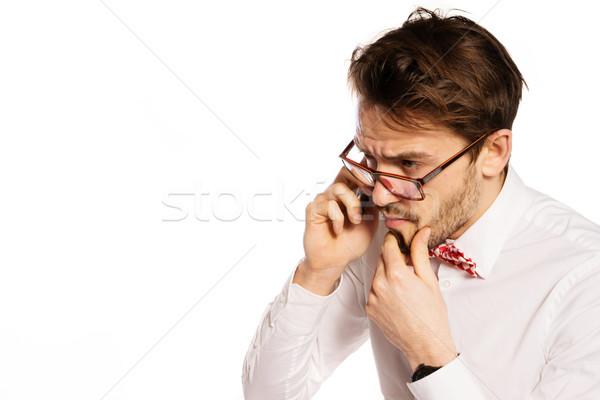 Nerdy businessman talking on a smartphone Stock photo © stryjek