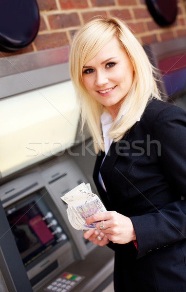 Woman with money at automatic teller Stock photo © stryjek