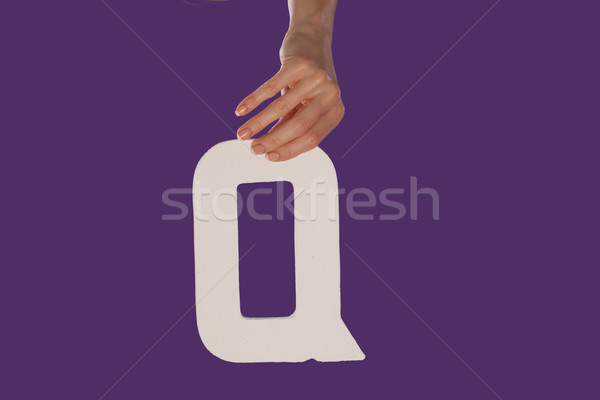 Female hand holding up the letter Q from top Stock photo © stryjek