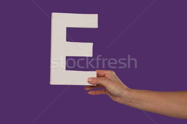 Female hand holding up the letter E from the right Stock photo © stryjek