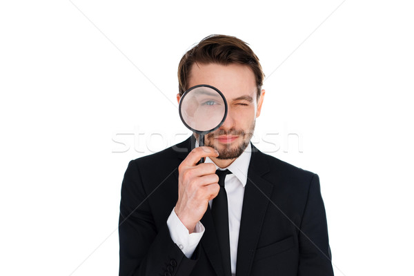 Businessman looking through a magnifying glass Stock photo © stryjek