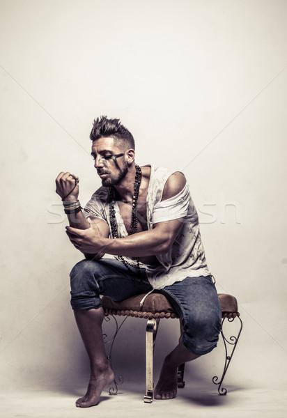 Szegény erős fiatalember szék ököl ruházat Stock fotó © stryjek
