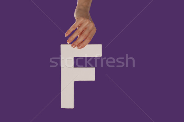 Female hand holding up the letter F from top Stock photo © stryjek