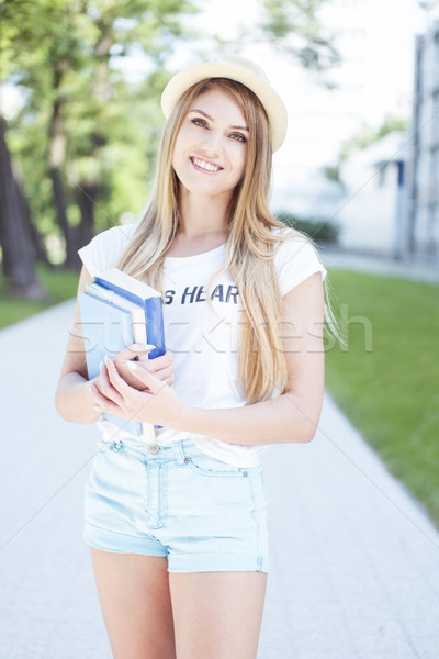 Cheerful Student Girl Holding Books at the Walkway Stock photo © stryjek