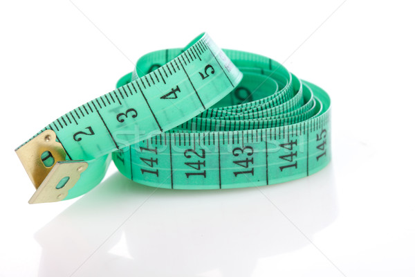 Green measuring tape, symbol of accuracy, on white Stock photo © stryjek