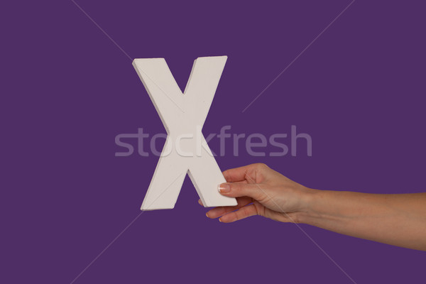 Female hand holding up the letter X from the right Stock photo © stryjek