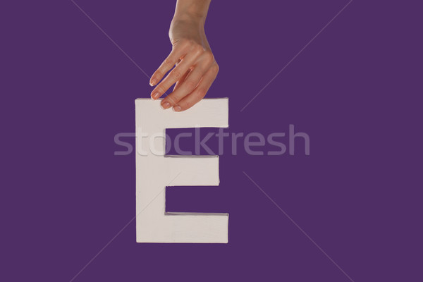 Female hand holding up the letter E from top Stock photo © stryjek