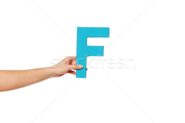 Stock photo: hand holding up the letter F from the left