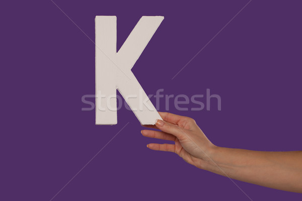 Female hand holding up the letter K from the right Stock photo © stryjek