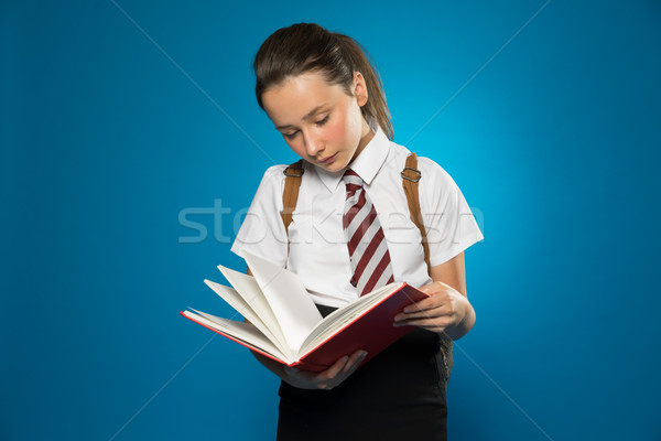 Young schoolgirl reading from a class text book Stock photo © stryjek