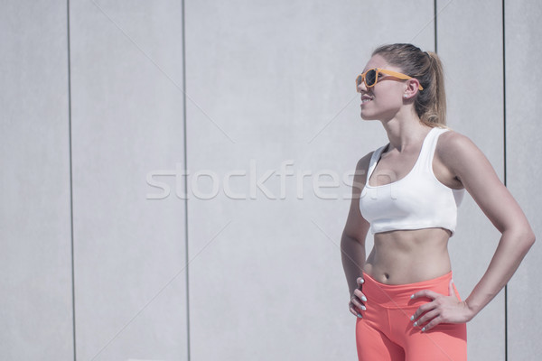 Fit Woman in Fitness Attire Standing Against Wall Stock photo © stryjek
