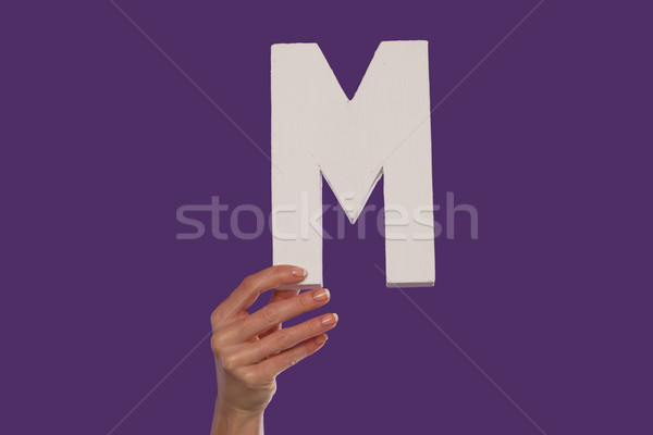 Female hand holding up the letter M from the bottom Stock photo © stryjek