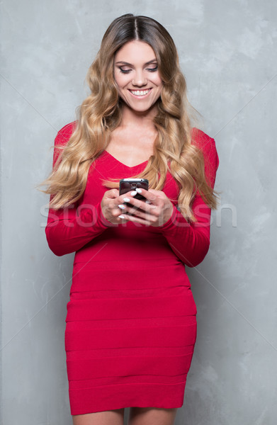 Attractive young woman in a red dress using smartphone Stock photo © stryjek