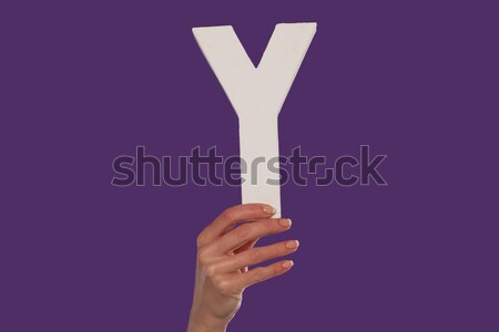 Female hand holding up the letter v from top Stock photo © stryjek