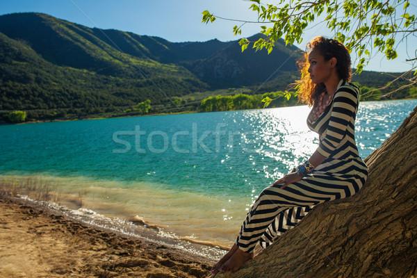 Beautiful woman posing on a tree trunk Stock photo © stryjek